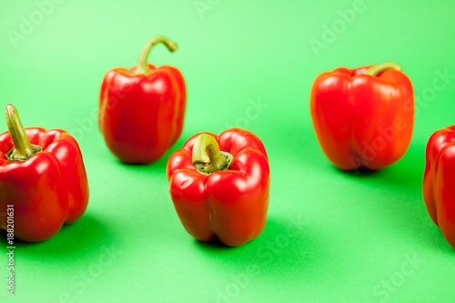 Foto Murales Group of fresh healthy sweet red pepper on green background