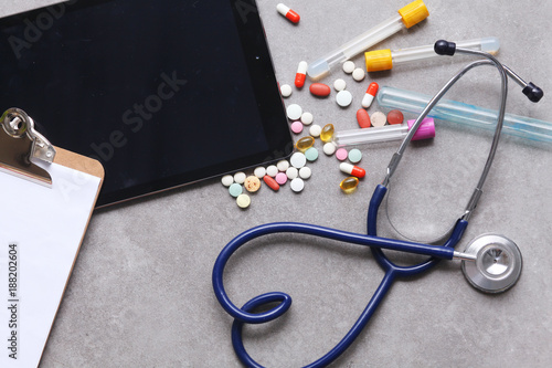 Foto Murales Medical equipment: blue stethoscope and tablet on gray background.