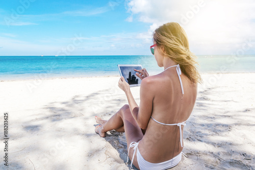 Foto Murales Happy young woman with a tablet in a tropical paradise resort. Communication during the holidays