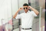 Portret chłopaka w białej koszuli z okularami przeciewsłonecznymi - 188205459
