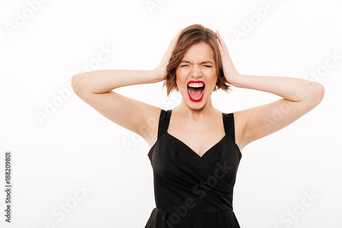 Portrait of a frustrated girl dressed in black dress screaming
