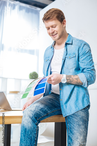 Foto Murales Perfect colors. Skilled experienced handsome designer smiling and feeling glad while sitting on the table and looking at the beautiful color palettes in his hand