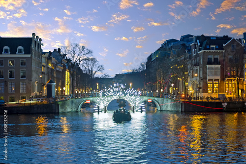 Amsterdam lights in the city center at the river Amstel in the Netherlands at su Poster