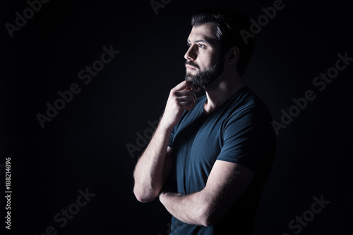 Involved in thoughts. Serious nice brutal man holding his chin and being thoughtful while standing against black background