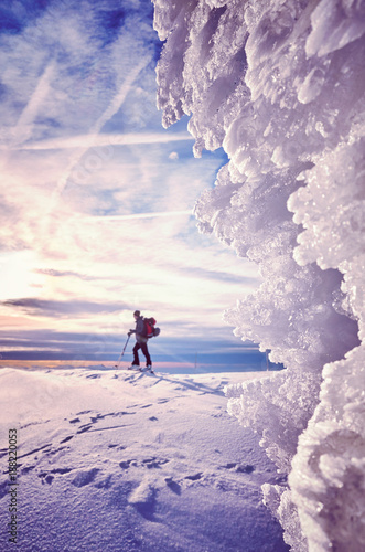 Foto Murales Ice formations with cross-country skier silhouette in distance at sunset, color toned picture, Karkonosze National Park, Poland.