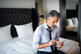 Mature businessman with smartphone in a hotel room. - 188221496