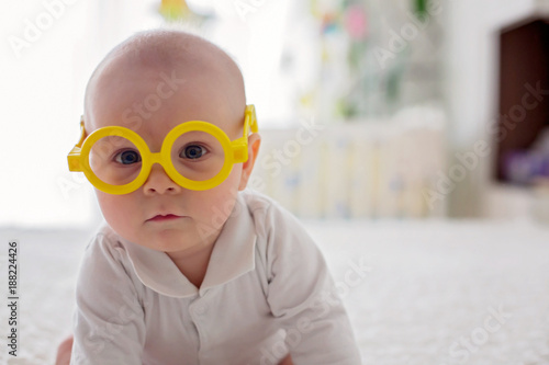 Foto Murales Little baby boy, toddler, playing at home with funny eye glasses in bed