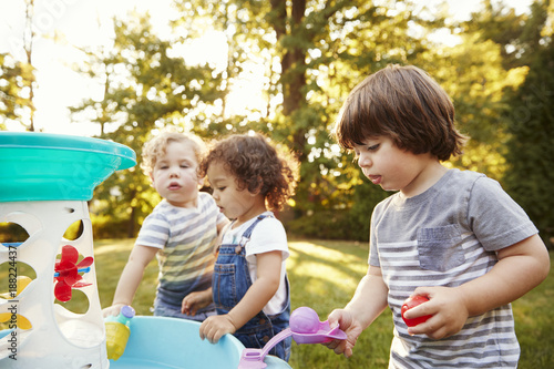 Foto Murales Group Of Young Children Playing With Water Table In Garden
