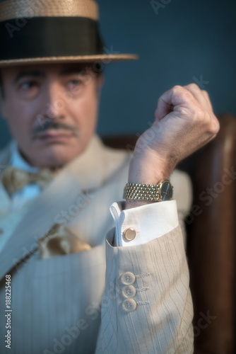 Forearm with golden watch of retro 1920s man in suit.