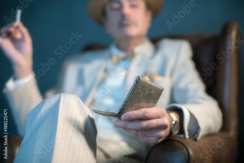 Hand of retro 1920s gangster holding cigarette box.