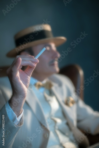 Hand holding cigarette. Retro 1920s upper class man in hat and suit.