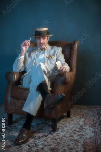 Vintage 1920s gangster with cigarette sitting in chair.