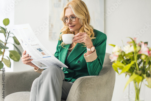 Poster beautiful middle aged businesswoman drinking coffee and reading newspaper