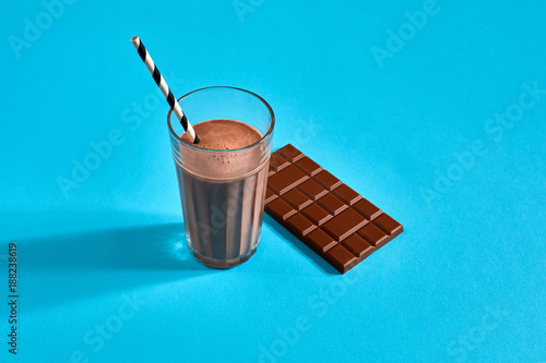 Papiers peints Lait, Milk-shake Glass of chocolate milk with chocolate bar on blue background with space for text or design
