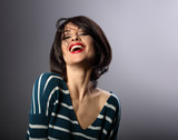 Happy loudly laughing with wide open mouth young woman with short hair in fashion sweater. portrait - 188244034