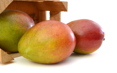 fresh mango fruit in a wooden box on a white background