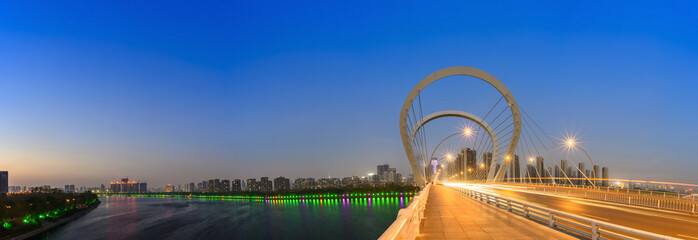 Modern bridge and skyscraper at dusk. Located in Shenyang, Liaoning, China.