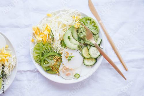 Foto Murales Green plant based salad bowl overhead spring vegan diet food concept