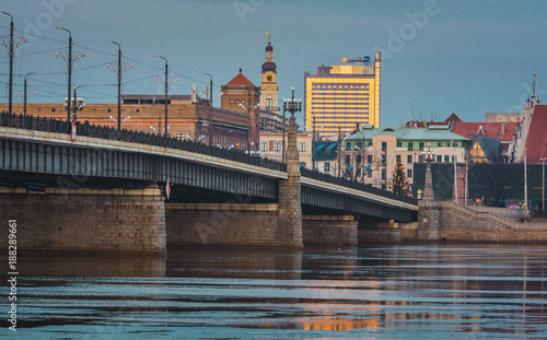 Foto Murales Picturesque view on the modern architecture of Riga panorama over the river with blue sky in background. Lights creating reflections in river.