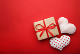 Gift box with fabric hearts on red background - 188292873