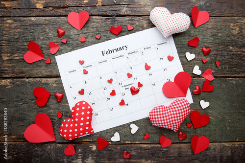 Foto Murales Fabric and paper hearts with february calendar on wooden table