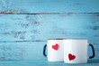 Mugs of tea with red heart on wooden table