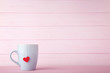Cup of tea with red heart on pink background