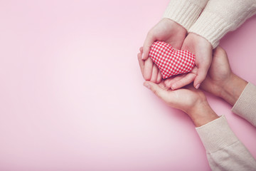 Female and male hand holding red fabric heart on pink background