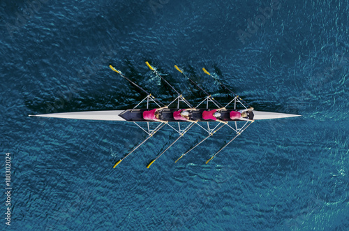 Leinwanddruck Bild Women's rowing team on blue water