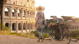 Young woman tourist with bycicle takes pictures of the colosseum in rome at sunset with smartphone. Beautiful stylish dress with large hat, flowers and bread in basket.