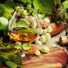 Brandy in a glass and fresh grapes with leaves and a vine, still life in rustic style, vintage wooden background, selective focus