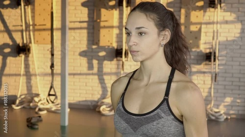 Fridge magnet The portrait of young woman who does front dumbbell raises during workout in the gym. The caucasian female athlete exercises her arm muscules with weight equipment standing in the bright room in
