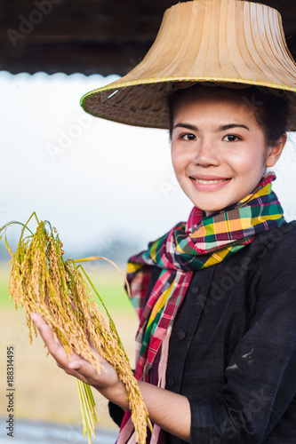Foto Murales farmer woman holding rice and sitting in cottage at rice field