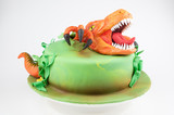 Art cake with orange dinosaur, decorated with green leaves. Gift for the boy. Picture for a menu or a confectionery catalog.