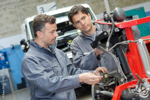mechanics fixing plow on the tractor