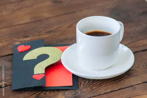 A cup of black coffee and a card on a wooden backdrop.
