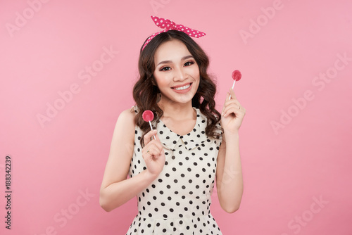 Plakat Fashion asian woman holding lollipop, posing against pink background