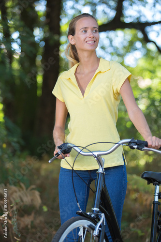 young lady standing in the forest with bicycle