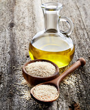 Sesame oil with seeds on wooden background - 188347072