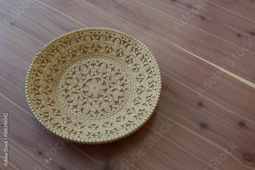 Decorative birch bark bowl, cut and stamped design, on wood background, copy space, horizontal aspect - 188348042
