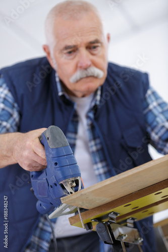 Foto Murales an elderly carpenter working with a band saw