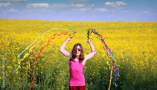 Foto Murales happy little girl playing with colorful ribbons spring season