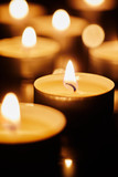 Burning tea light candles in darkness - 188365646
