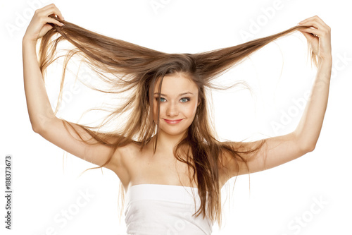 young blonde showing her long straight hair on white bckground