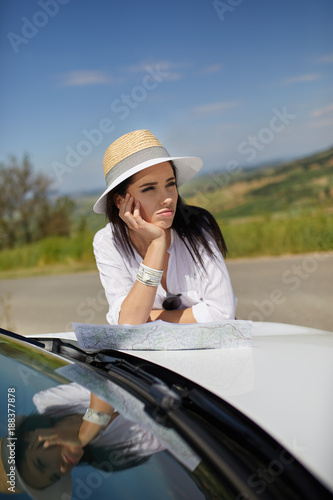Young woman got lost in the field while driving a car and reading paper map