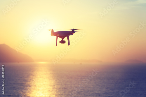 Deurstickers Zwavel geel silhouette of flying drone which taking photo over sunrise sea.