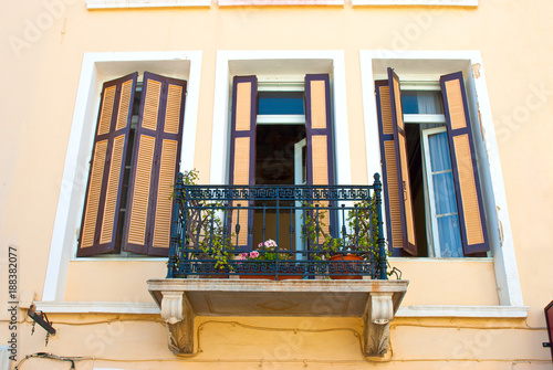 Windows with balcony on the wall of a house in Greece
