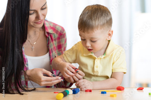 child kid boy and mother play colorful clay toy at nursery or kindergarten © Oksana Kuzmina