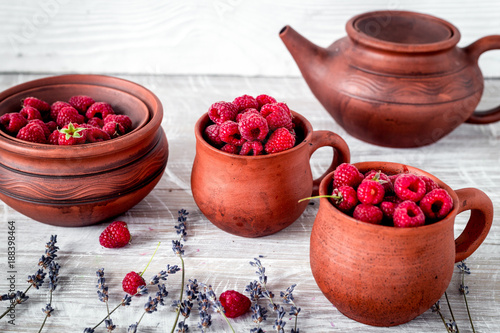 Sticker raspberry in pottery cup with lavander and pot on wooden backgro