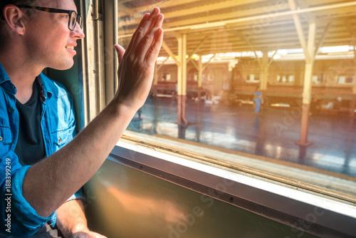 Fototapeta Man sitting in a train raise his hand to say hello or goodbye